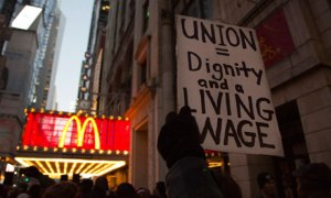 A protester holds up a sign at a demonstration outside McDonald's in Times Square in New York